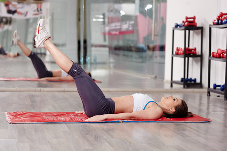 Young woman doing abs workout in a gym on a mat photo
