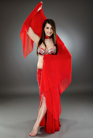 Beautiful ethnic bellydancer performing oriental dance in traditional costume photo