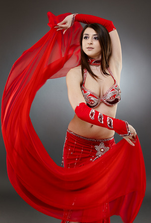 Beautiful ethnic bellydancer performing oriental dance in traditional costume