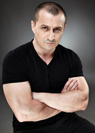 desconfianza: Primer plano de un hombre con una expresi�n de desconfianza, sobre fondo gris