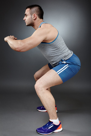 doings: Young athletic man doings squats, studio shot Stock Photo