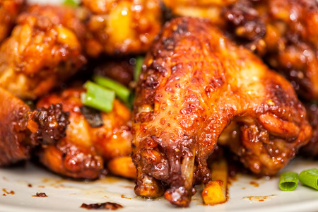 Closeup of caramelized asian chicken wings with selective focus photo