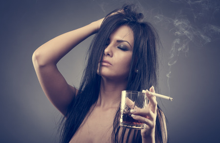 Sexy gorgeous brunette young woman with a strong migraine, holding a glass of brandy and a cigarette photo