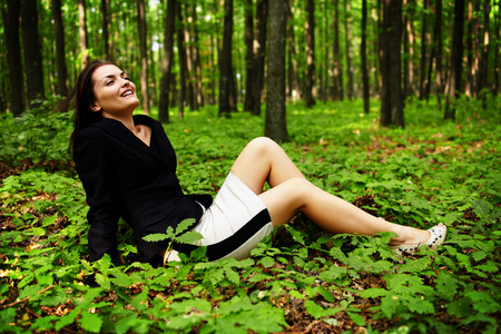 Lomo style image of a businesswoman sitting on leaves in a forest photo
