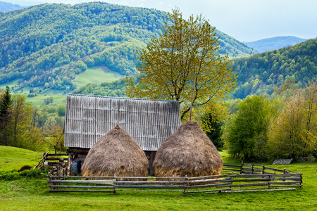 Landscape with an old shed and haystacks in the mountains photo