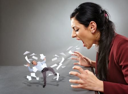 conceptual image: Conceptual image of an angry lady boss yelling and blowing away an employee in a hurricane of paperwork Stock Photo