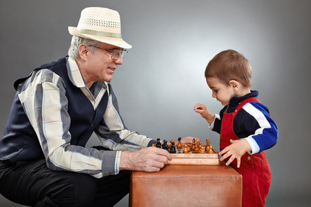 Grandpa and grandson playing a game of chess over gray background photo
