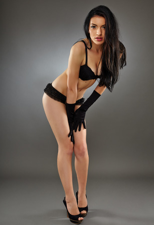 Glamour hispanic woman model posing in black lingerie over gray background photo