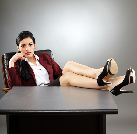 table skirt: Relaxed woman CEO putting her legs up on the desk