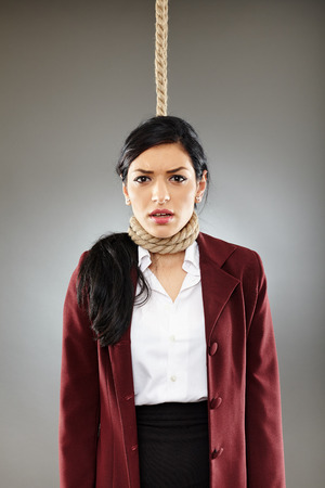 punished: Scared business woman with noose around her neck, about the get hanged Stock Photo