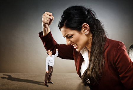 subordinate: Angry businesswoman ready to crush the courageous subordinate who is confronting her Stock Photo