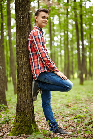 boy alone: Trendy and handsome teenage boy in plaid shirt, outdoor in a forest Stock Photo