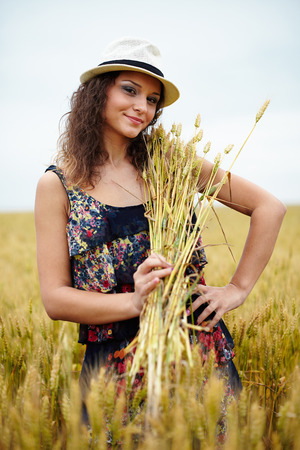 A happy caucasian young and beautiful woman in a wheat field photo