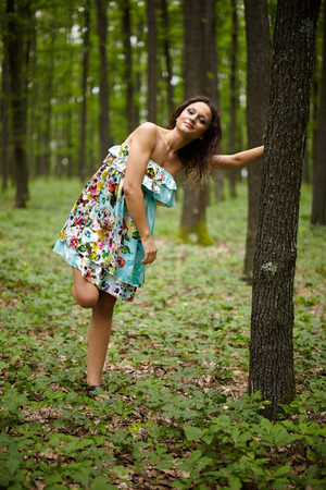 blurred people: Beautiful young caucasian woman posing outdoor in the woods