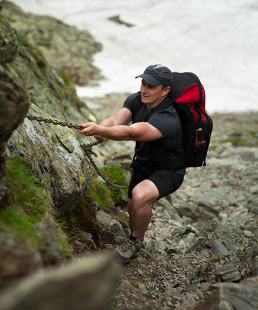 climbing cable: Man with heavy backpack climbing on safety cable on a mountain Stock Photo