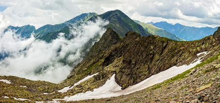 fagaras: Panorama of Fagaras mountains in Romania with clouds Stock Photo