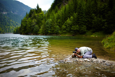 Professional nature photographer outdoor at a lake photo