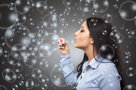 blowing bubbles: Businesswoman blowing a lot of soap bubbles, business metaphor for ephemeral and shallow ideas