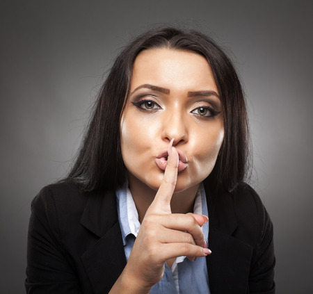 Hispanic young businesswoman with finger on lips, making silence sign photo
