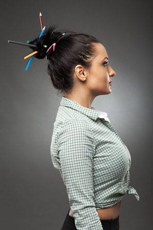 Latin girl with unusual geisha hairdo and hair sticks out of colored pencils photo