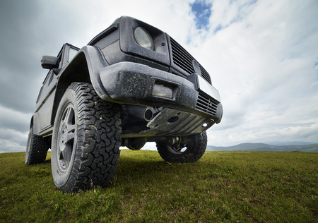 A black offroad all terrain vehicle on a green pasture in the mountains