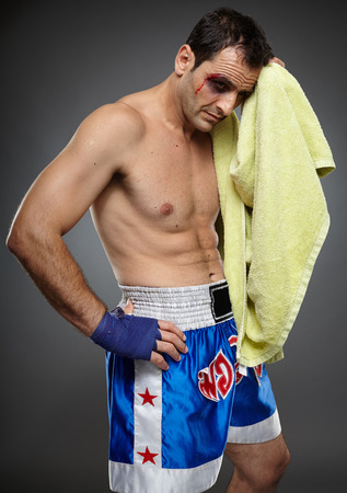 bruised: Bruised and injured fighter with towel after a difficult match Stock Photo