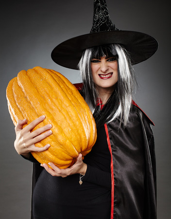 large pumpkin: Young witch with hat and cape holding a large pumpkin Stock Photo