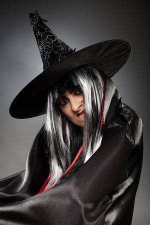 witchery: Young mean witch in cloak Stock Photo