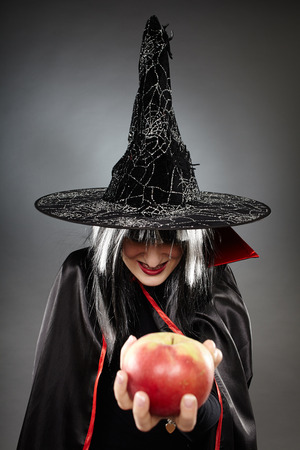 Tricky witch offering a poisoned apple, Halloween theme photo