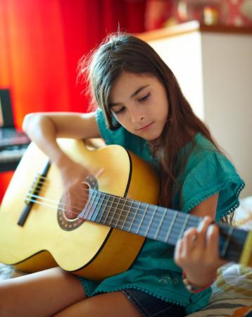clases: Niña linda que juega la guitarra cubierta en su dormitorio