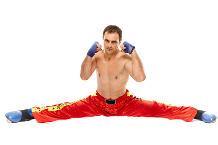 Kickbox or muay thai fighter executing a split, isolated on white background photo