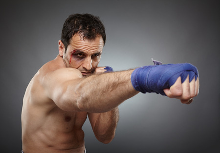 muay: Muay thai or kickbox fighter with bruises and blood on his face, throwing a direct punch Stock Photo