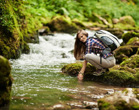 Young European woman hiker by the river, outdoors activities