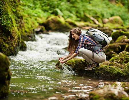 Young European woman hiker by the river, outdoors activities photo