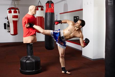 Kickboxer mit dem Dummy in der Turnhalle Standard-Bild - 31693298
