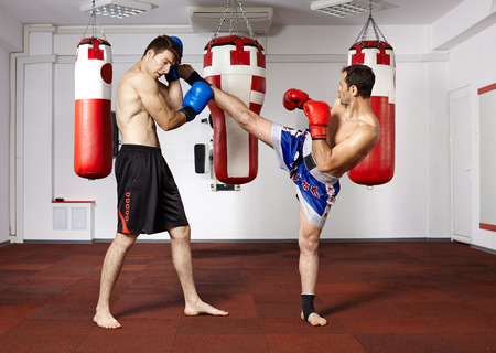 Two young kickbox fighters training in the gym photo