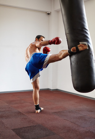 Kickbox fighter training in the gym with the punch bag photo