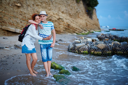 Happy mother and son at seaside on the beach near the cliff photo