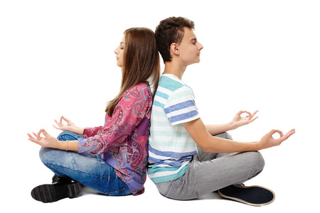 Teenagers friends or classmates sitting back to back in yoga meditation posture