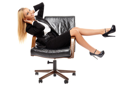 Young positive caucasian businesswoman sitting in her CEO chair, isolated on white photo