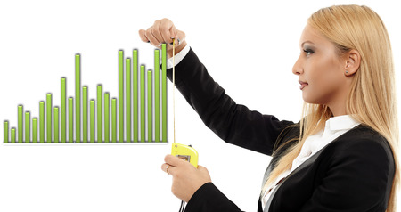 evaluating: Young busineswoman evaluating a chart with a measuring tape, concept image of success