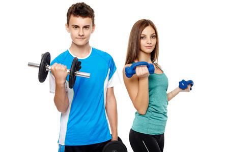 hombres guapos: Dos adolescentes chico y chica haciendo ejercicios de gimnasio con pesas aislados sobre fondo blanco