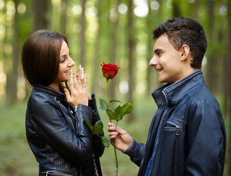 Teenage romance - a boy giving a flower to his girlfriend, outdoor in the park photo