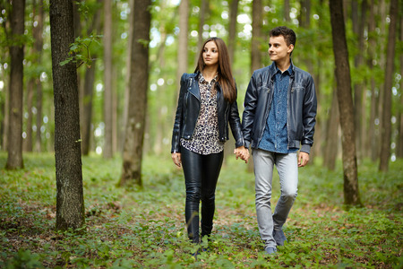 Teenagers boy and girl on a date, taking a walk through the forest photo