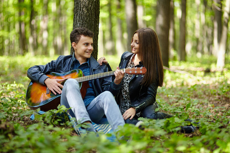 Teenager playing guitar for his girlfriend outdoor in the forest photo