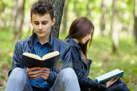 Teenagers students boy and girl reading outdoor in a forest photo
