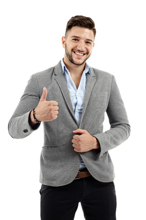 Successful young businessman showing thumbs up sign isolated on white photo