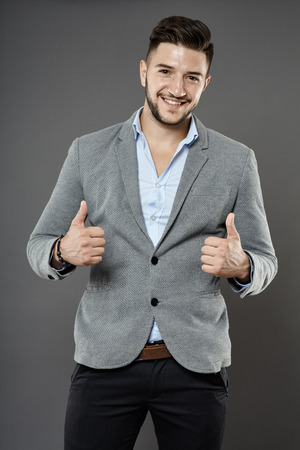 Young businessman showing thumbs up sign, studio shot photo