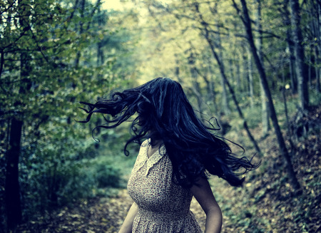 fearful: Scared young woman running through a forest at night, looking back Stock Photo