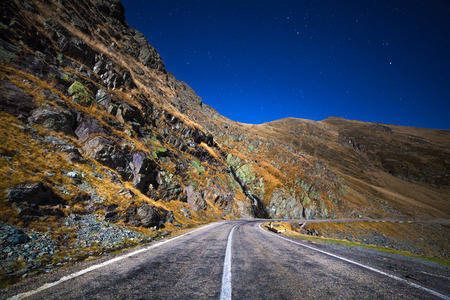 Landscape with mountains and an empty highway at night, under starry sky photo